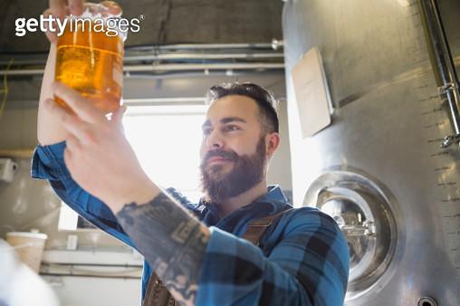 Brewery worker examining beer in beaker - gettyimageskorea