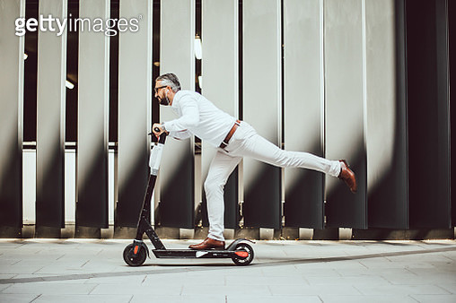 Elegant man rides his electric scooter in the big city - gettyimageskorea