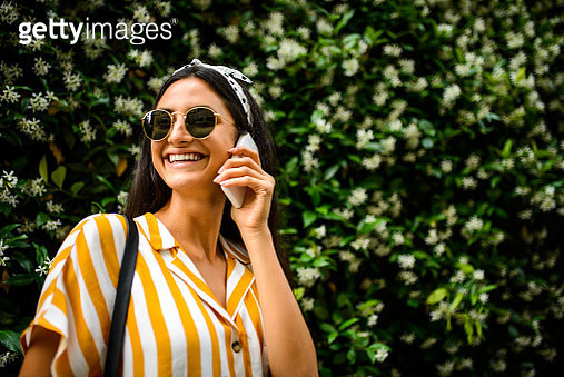 Smiling woman talking on the phone. - gettyimageskorea