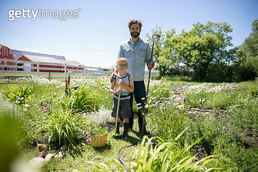 Portrait smiling father and son gardening on sunny rural farm - gettyimageskorea