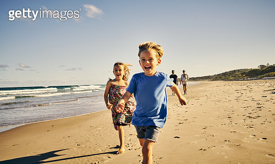 Shot of two adorable little children running at the beach with their parents in the background - gettyimageskorea
