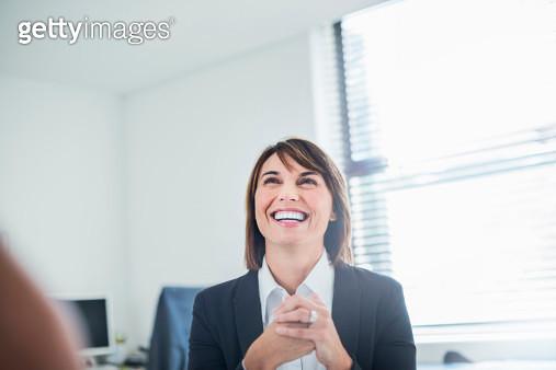 Smiling businesswoman in her office - gettyimageskorea