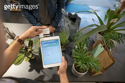 Overhead view male shop owner swiping digital tablet credit card payment in plant shop - gettyimageskorea