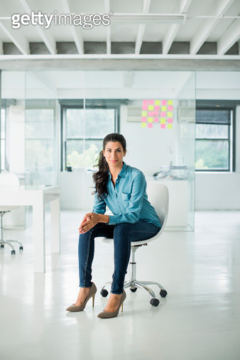 Businesswoman sitting on a chair in open office looking into camera - gettyimageskorea