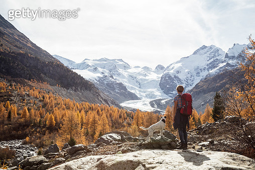A woman and her dog are hiking in Switzerland. Large file - gettyimageskorea