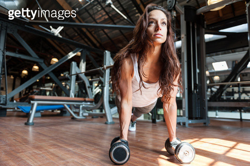 Young woman at gym doing pushups on dumbbells - gettyimageskorea