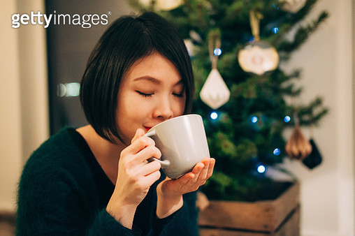 Young woman having hot coffee at home in front of Christmas tree - gettyimageskorea