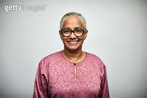 Portrait of senior woman smiling. Close-up of confident elderly female is wearing eyeglasses. She is in casuals over white background. - gettyimageskorea