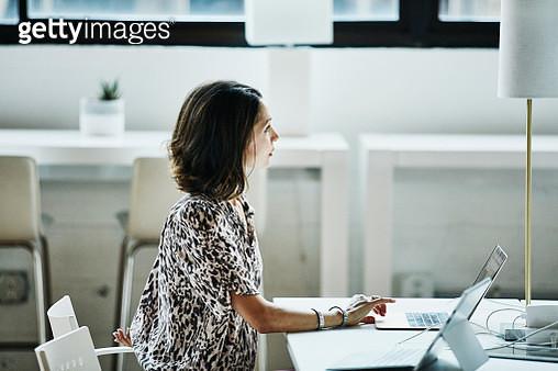 Businesswoman working on laptop in coworking office - gettyimageskorea