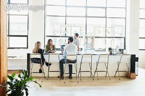 Colleagues having informal meeting in coworking office kitchen - gettyimageskorea