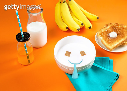 Breakfast scene with bowl of cereal arranged in a smiley face, juice, milk, bananas and toast on orange background - gettyimageskorea