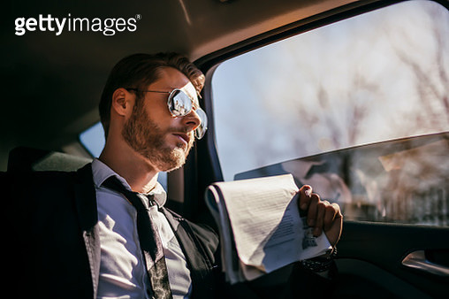 Businessman in car with news paper - gettyimageskorea