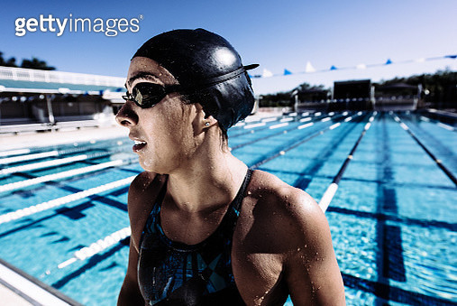 Swimmer in swimming cap and goggles catching breath by pool - gettyimageskorea
