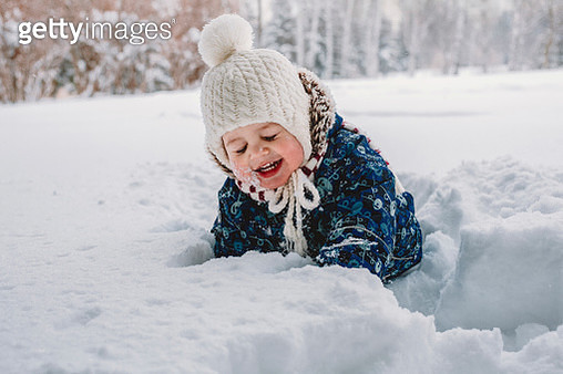 Cute happy baby boy standing on snow covered field in park - gettyimageskorea