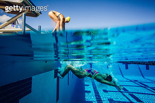 Swimmer on diving board and swimmer in pool - gettyimageskorea