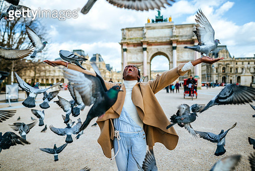 France, Paris, Happy young woman with flying pidgeons at Arc de Triomphe - gettyimageskorea