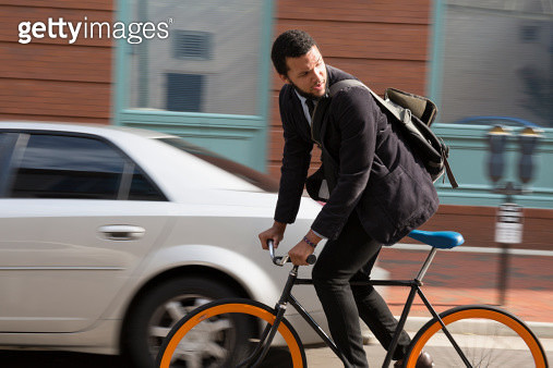 Mixed race businessman riding bicycle on city street - gettyimageskorea