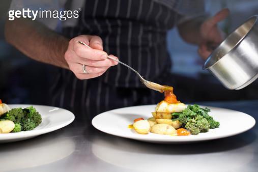 Chef preparing dish in kitchen - gettyimageskorea