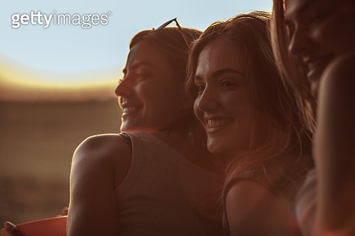 Close up shot of three cheerful young females smiling and relaxing together while enjoying beautiful summer sunset on their road trip. - gettyimageskorea