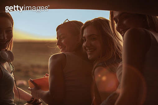 Four cheerful girlfriends sitting in the open trunk of a car on their rest stop from a road trip and enjoying together beautiful summer sunset. - gettyimageskorea