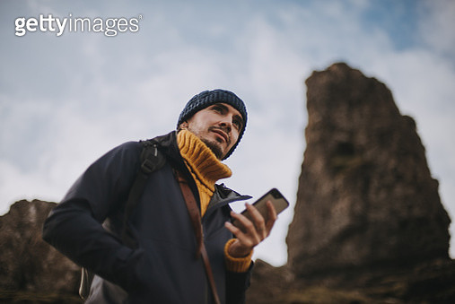 Young man standing in front of stone Spire 'The Old Man of Storr', Isle of Skye, Scottish Landscape - gettyimageskorea