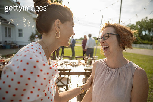 Women friends talking and laughing at wedding reception in sunny rural garden - gettyimageskorea