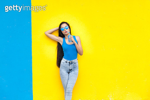 Woman drinking and standing in front of colorful wall background - gettyimageskorea