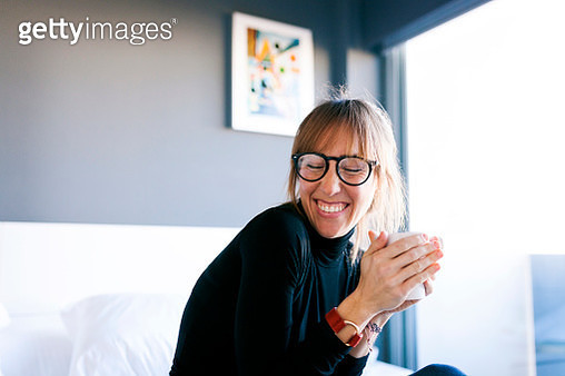 Happy young woman at home drinking cup of coffee - gettyimageskorea
