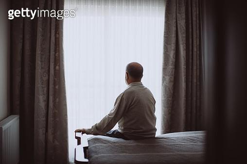 Elderly man sitting on bed looking serious - gettyimageskorea