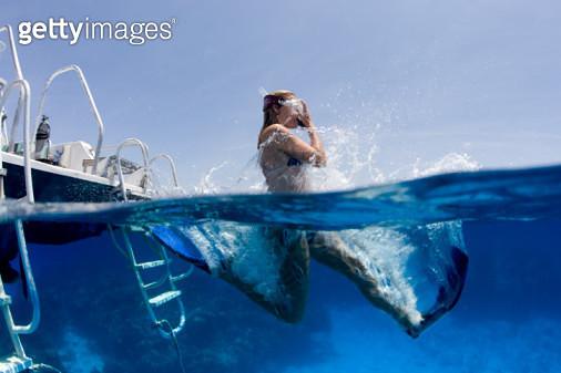 Snorkeler Enters Water from Boat - gettyimageskorea