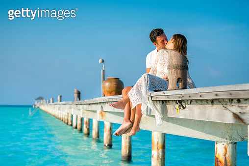 Adult Couple Kissing on Pier - gettyimageskorea