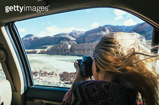 Woman takes pic out car window in mountain landscape - gettyimageskorea