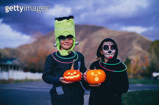 Two young children, a boys and a girl, are dressed as a skeleton and Frankenstein for Halloween. They are ready to trick or treat for candy while holding illuminated Jack O' Lanterns in a local residential neighborhood. Image taken in Utah, USA. - gettyimageskorea