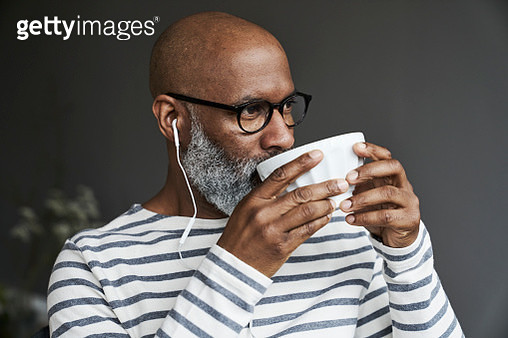 Mature man with earphones drinking coffee - gettyimageskorea