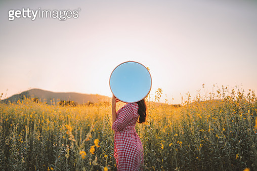 Woman Holding Mirror Against Face While Standing Outdoors - gettyimageskorea