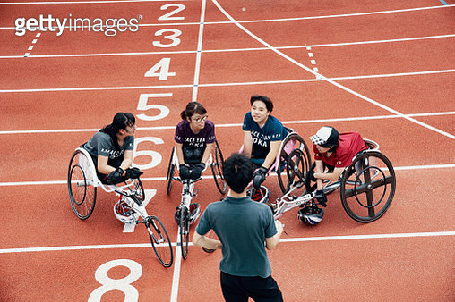 Young female wheelchair racers training together at an outdoor track with their coach - gettyimageskorea
