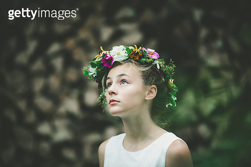 young girl standing next to a stack of trees while wearing a floral wreath, portrait. - gettyimageskorea
