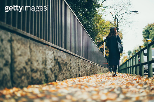 Rear view of young woman walking in city street on the way to work on a breezy Autumn morning - gettyimageskorea