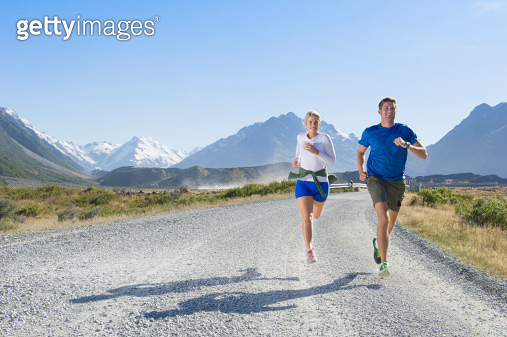 Caucasian couple running on rural road - gettyimageskorea