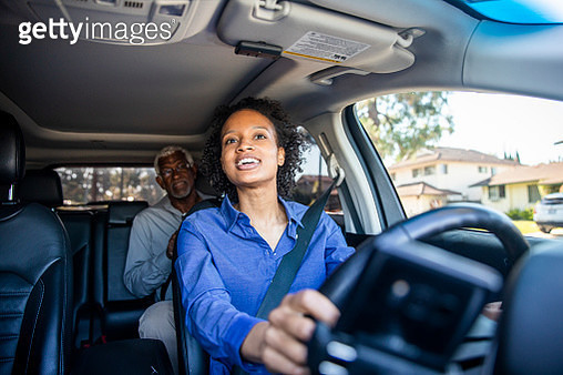 A young black woman drives a passenger in her car as a professional driver. - gettyimageskorea