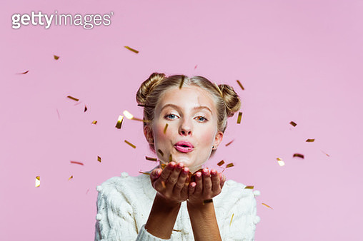 Portrait of teenager wearing white sweater, blowing gold confetti at the camera. Studio shot on pink background. - gettyimageskorea