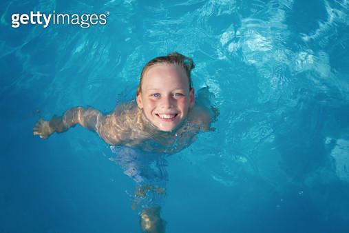 Happy boy swimming in pool - gettyimageskorea