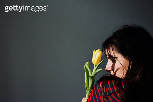 Woman Holding Flower Against Gray Wall - gettyimageskorea