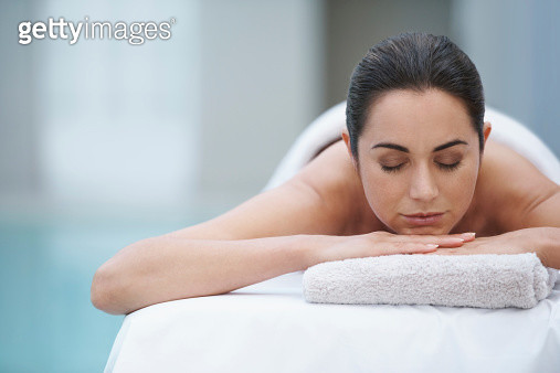 Cropped shot of an attractive woman lying on a massage table beside a pool at a spa - gettyimageskorea