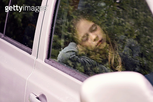 Girl sleeping in a car - gettyimageskorea