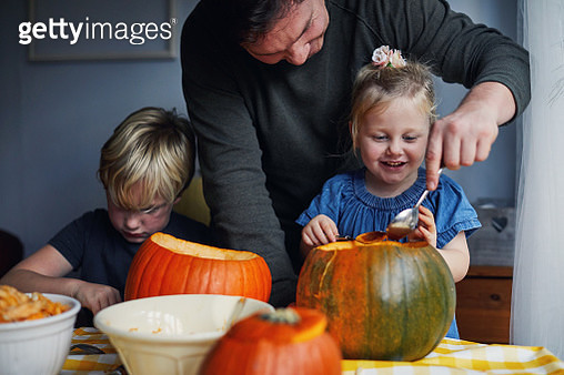 Family scooping out pumpkins together for Halloween - gettyimageskorea