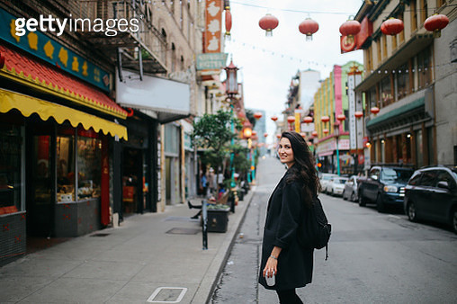 Young woman walking down the Chinatown district in San Francisco, California. She is wearing casual clothing, carrying a cup of coffee to go, enjoying the vibrant and famous Chinese district. - gettyimageskorea