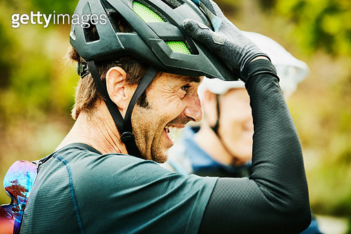 Laughing mature man hanging out with friends after mountain bike ride - gettyimageskorea