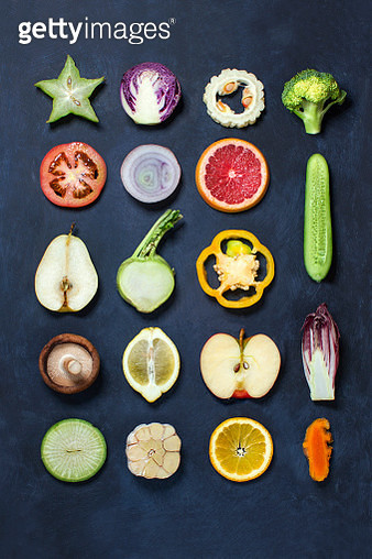 Cross sections of colourful vegetables and fruits on rustic moody blue background. - gettyimageskorea