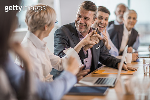 Happy businessman having fun while talking to his colleague on a meeting. - gettyimageskorea